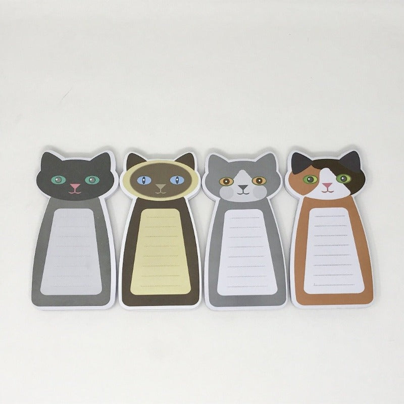Assorted collection of four cat-themed notepads laying flat on a white surface