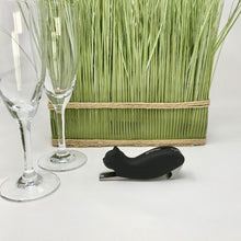 Picture of a black cat-themed bottle opener with two champagne glasses in front of it and green artificial grass to the side of it