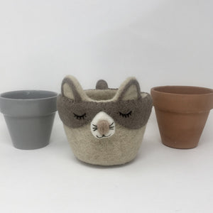 Grey and off-white felt cat plant holder with two ceramic pots on either side standing on an all white surface
