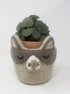 Grey and off-white felt cat plant holder with a plant inside of it standing on an all white surface