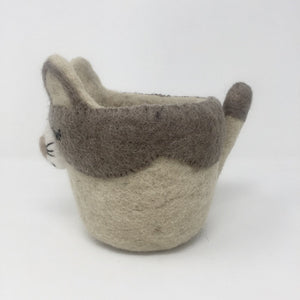 Grey and off-white felt cat plant holder standing on an all white surface