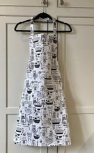 Picture of a white and black kitchen apron on a black hanger featuring black cats