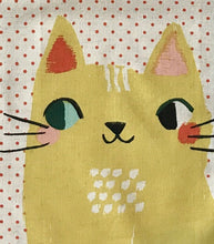 Close up picture of a white kitchen towel with red dots and two big yellow cats on it hanging from a white kitchen cupboard