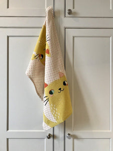 White kitchen towel with red dots and two big yellow cats on it hanging from a white kitchen cupboard