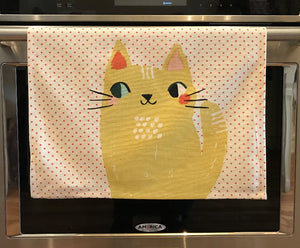 White kitchen towel with red dots and two big yellow cats on it hanging from an oven handle bar