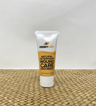 White tube of wound ointment for pets on a wicker surface
