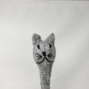 Close up of a grey colored felt cat pen laying on an all white surface