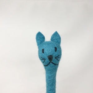 Close up picture of a turquoise blue colored felt cat pen laying on an all white surface