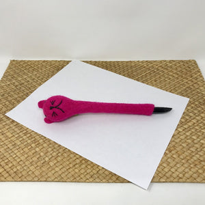 Picture of a shocking pink colored felt cat pen laying on a white sheet of paper on a wicker surface