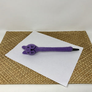 Picture of a lavender colored felt cat pen laying on a white sheet of paper on a wicker surface