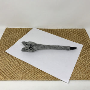 Picture of a grey colored felt cat pen laying on a white sheet of paper on a wicker surface