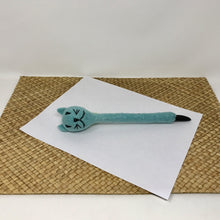 Picture of an aqua blue felt cat pen laying flat on a white sheet of paper which is on a wicker surface