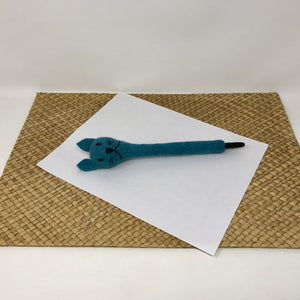Picture of a turquoise blue colored felt cat pen laying on a white sheet of paper on a wicker surface