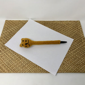Picture of a brown colored felt cat pen laying on a white sheet of paper on a wicker surface