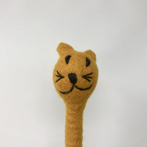 Close up picture of a brown colored felt cat pen laying on a white surface