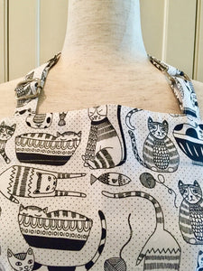 Close up picture of a black and white kitchen apron featuring black and white cats
