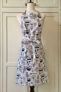 Picture of a white and black kitchen apron on a mannequin featuring black cats