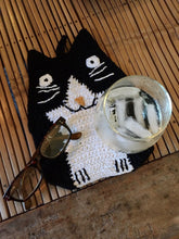 Picture of a black and white hand-knitted cat-themed drink coaster with a drink and glasses on it