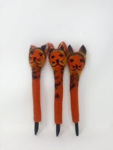 Picture of three orange and black striped felt cat pens laying on an all white surface