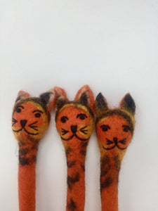 Close up picture of three orange and black striped felt cat pens laying on an all white surface