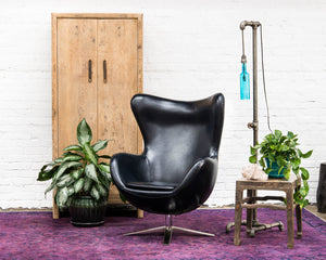 Mid-century style egg chair, covered in dark navy blue vegan leather