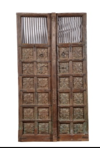 Antique Indian teak wood pair of doors from a Rajasthan Haveli, 49'' x 88''h, with carved lotus panels, traces of old paint and an iron bar top, very fine quality carvings. Found in Rajasthan