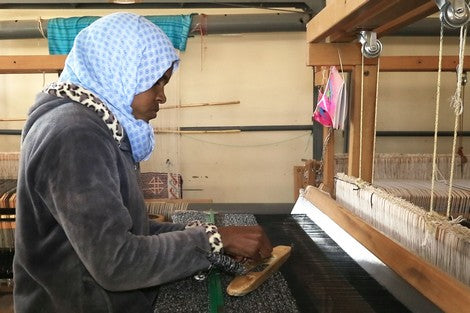 Moroccan woman weaving rug in artisanale cooperative