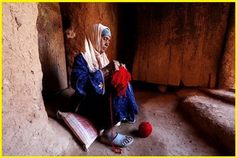 woman-working-moroccan-rug-red-wool