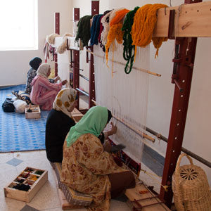 women weaving moroccan berber rug
