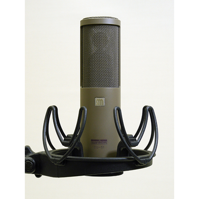 This is a photo of the Sanken CU-51. It is shown in a grey colour, in a front facing view. It is held in place by a black piece of equipment.