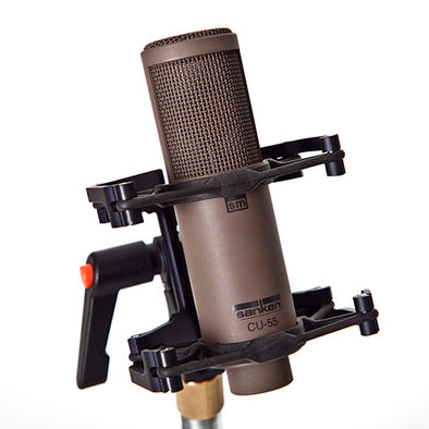 This is a photo of the Sanken CU-55 microphone. It is shown in a brown/grey colour. It is held in place by a piece of black equipment at an angled front view.