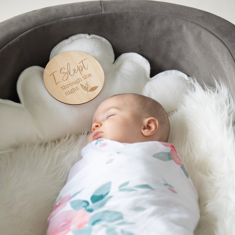 Swaddled baby sleeping with milestone disc in crib