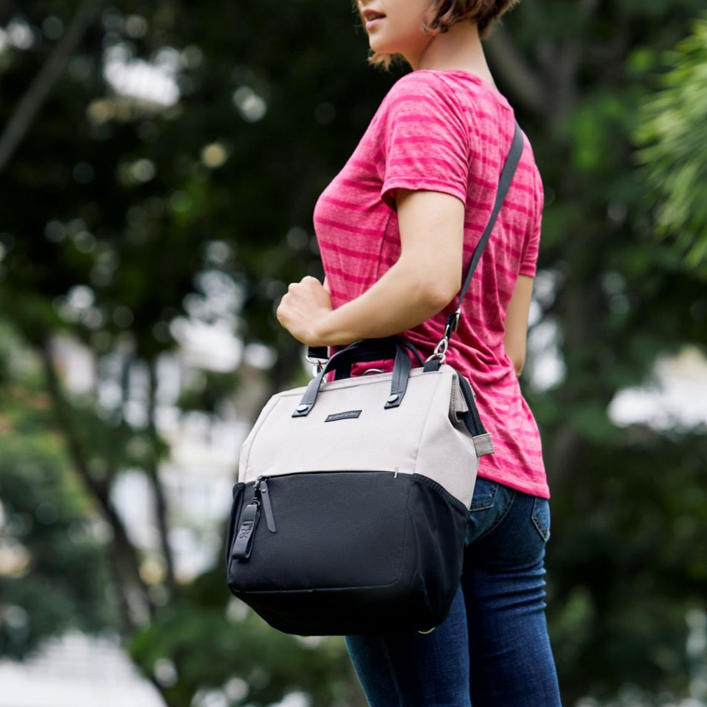 Light tan Handbag/Crossbody/Backpack made with recycled materials on a women walking outside
