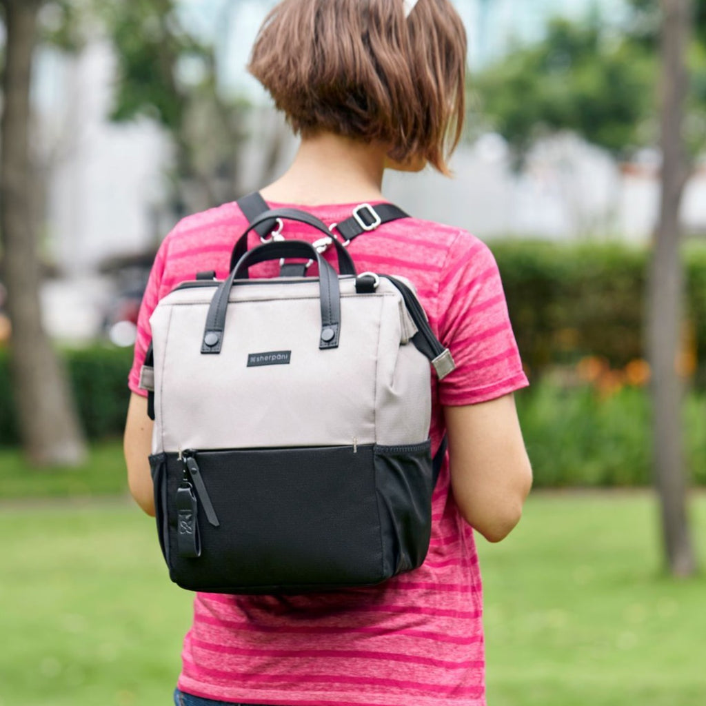 Light tan Handbag/Crossbody/Backpack made with recycled materials worn as a woman backpack walking outside