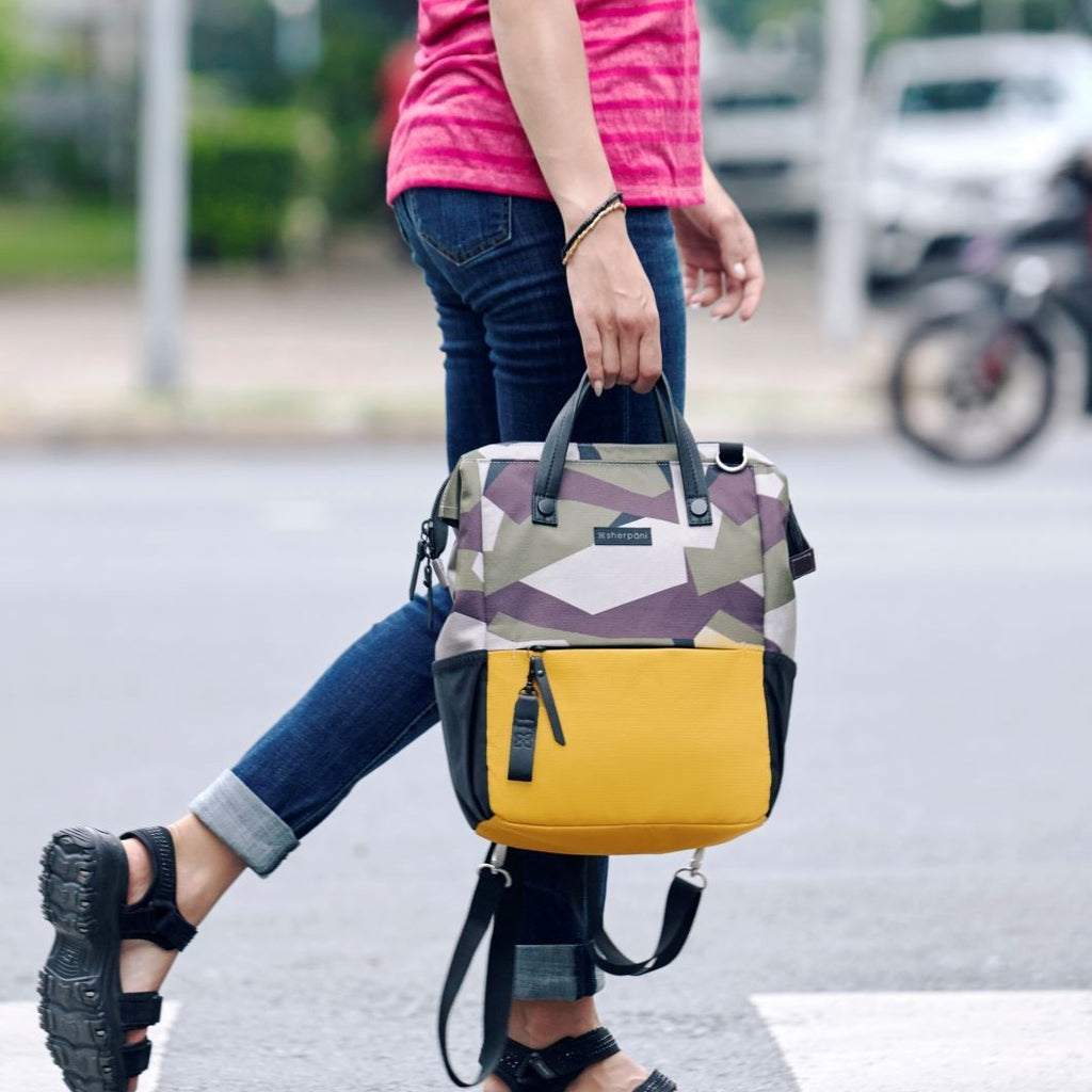 Camo & Yellow Handbag/Crossbody/Backpack made with recycled materials with a woman hanging out