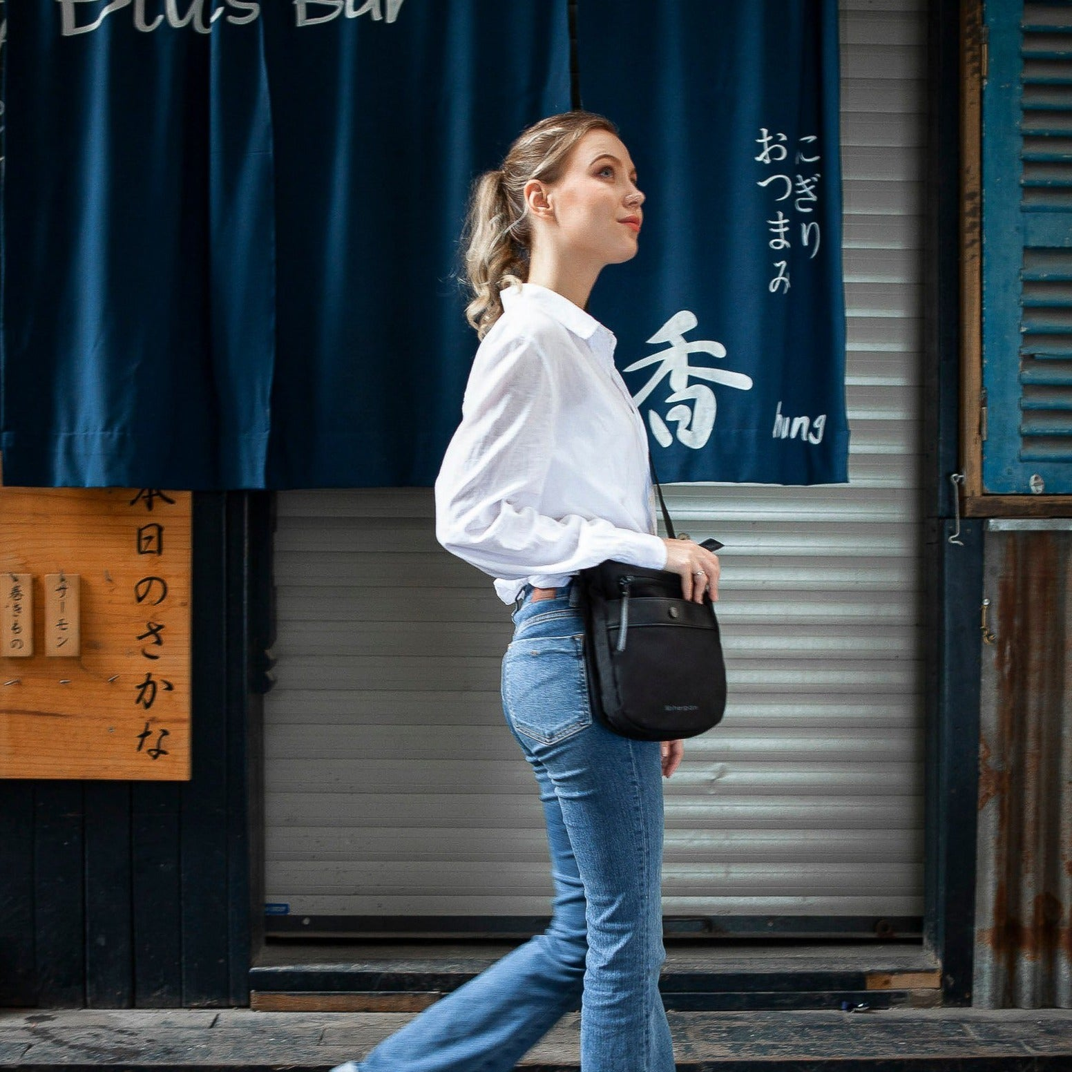 Black Anti-theft Crossbody with anti-theft features on a woman on street