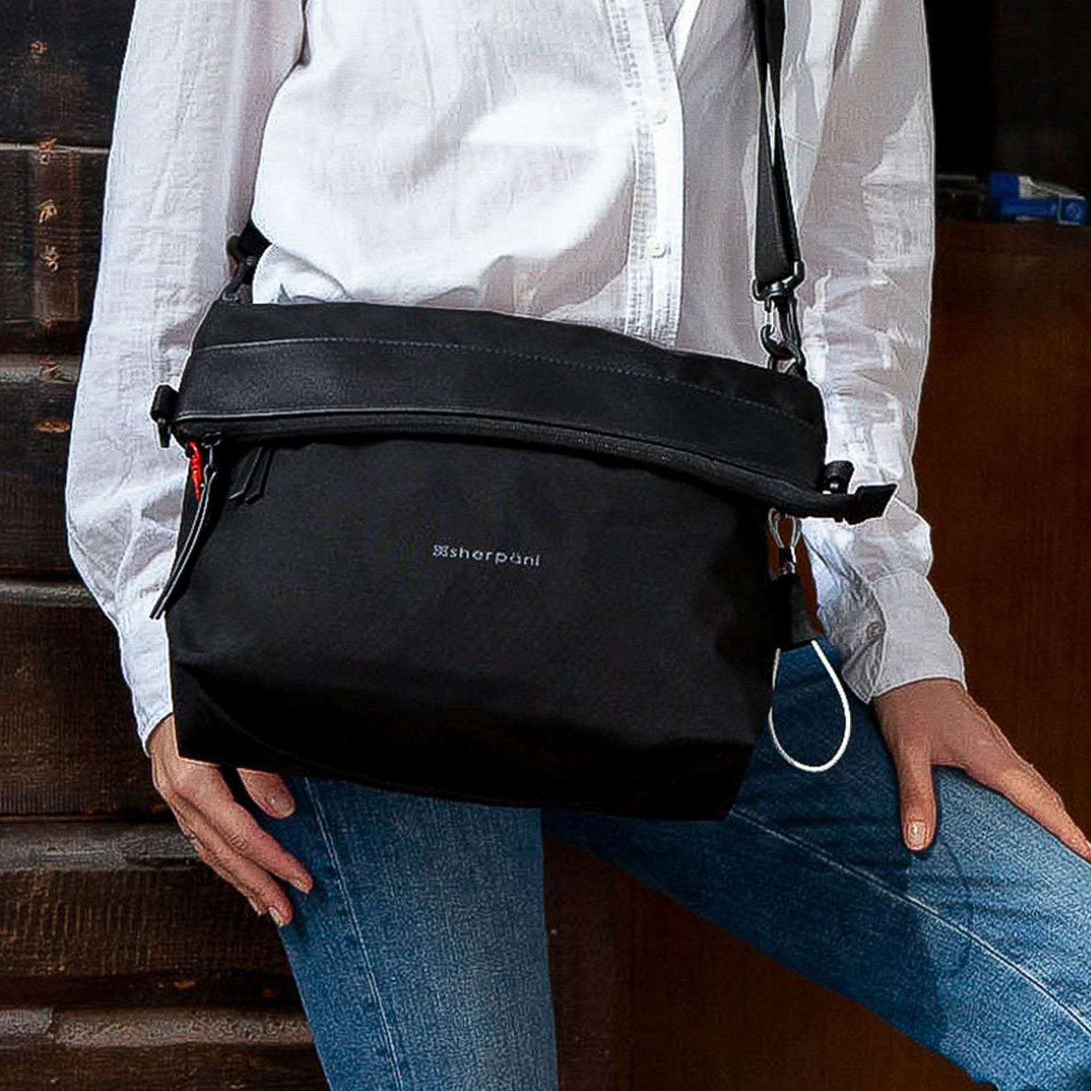 Black Anti Theft Reversible Crossbody (worn as crossbody) with anti-theft features on a woman walking outside