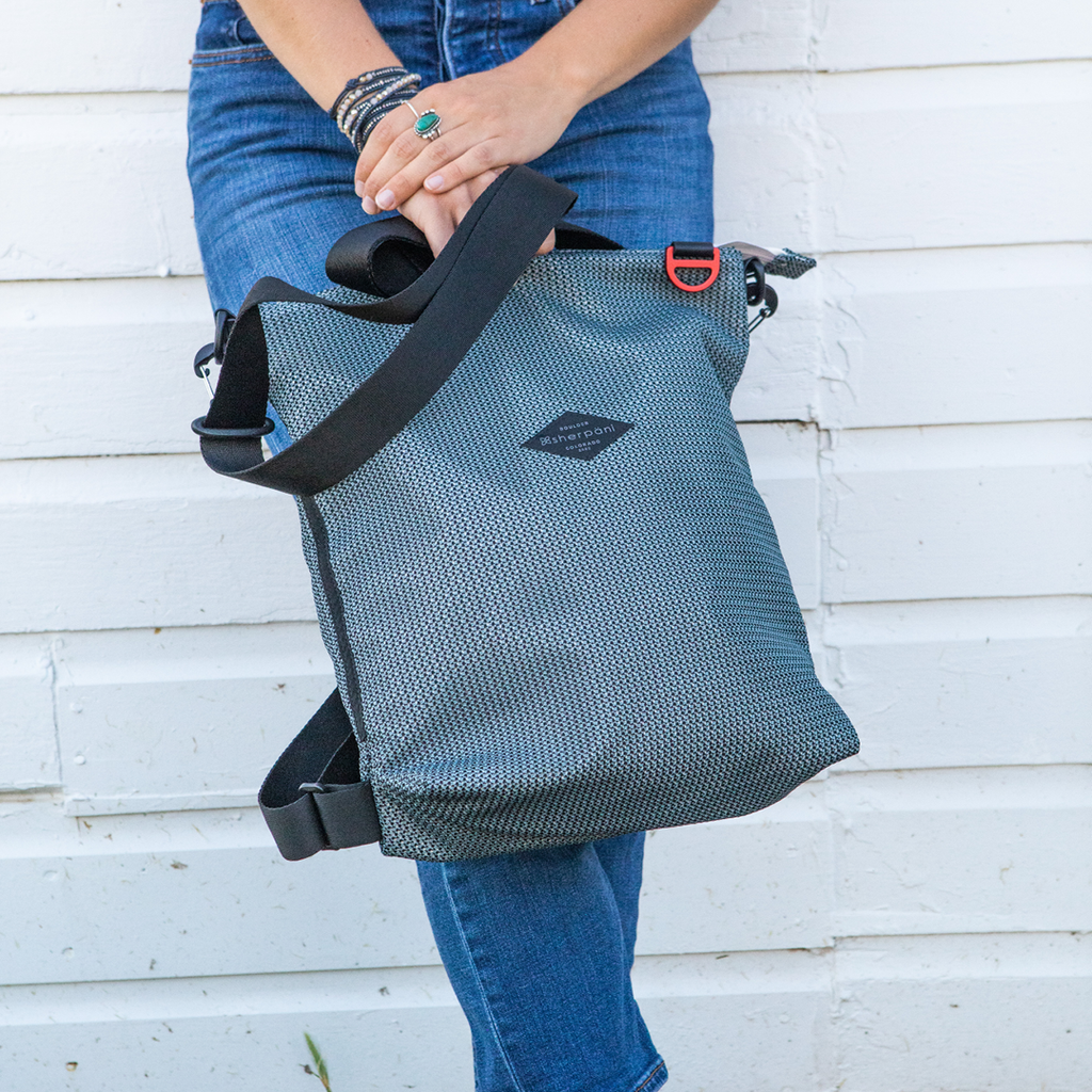 Black & Grey Convertible Backpack and Crossbody made with woven mesh worn on woman standing outside