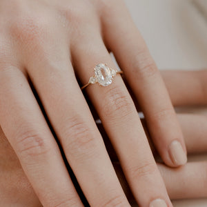Oval cut white sapphire engagement ring with diamond accents in 14k gold band