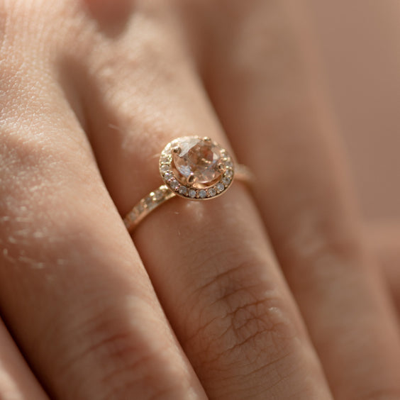 Halo Morganite Engagement Ring in a 14K yellow gold band features a round-cut morganite stone surrounded by a halo of diamonds