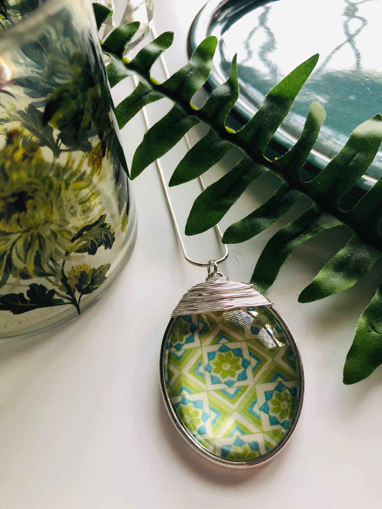 A large silver oval pendant with a mixture of green tones in a retro effect print and silver wire detailing