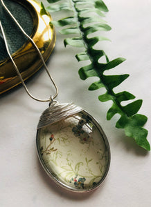 A large silver oval pendant with a light green botanical print pendant