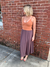woman leaning on red brick wall wearing orange crop top and purple skirt