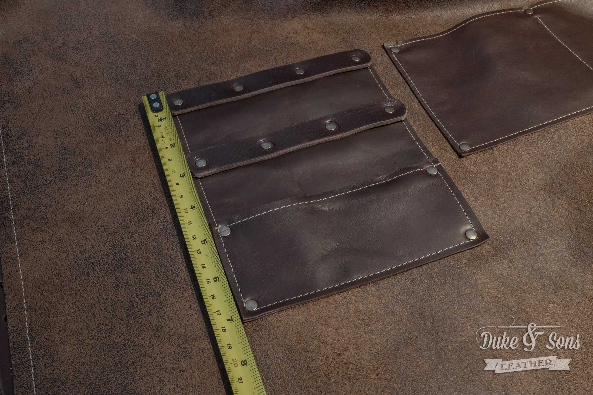 Barber apron, brown leather with pockets for shears and combs.