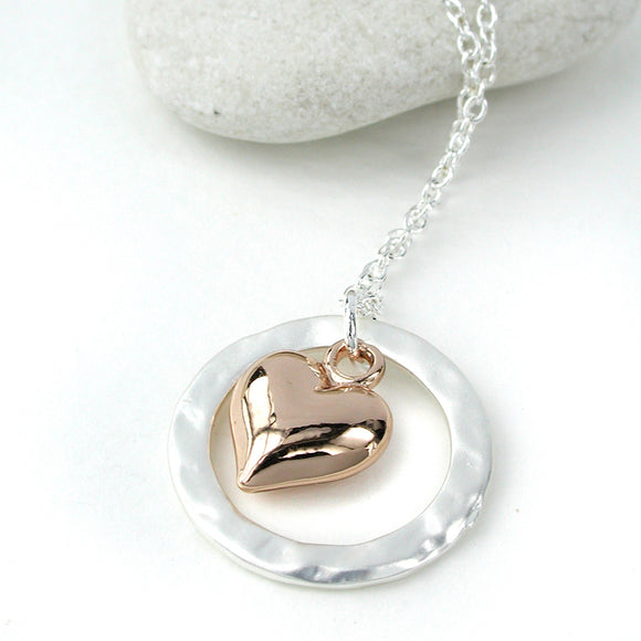 Silver plated necklace with a beaten circle in a matt finish and a rose gold plated puff heart