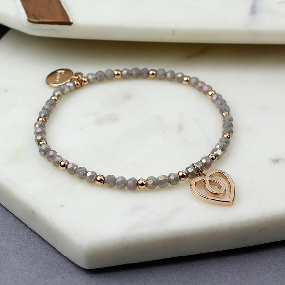 Grey pearlescent bead and rose gold bead stretch bracelet with a twist heart in a rose gold style finish.