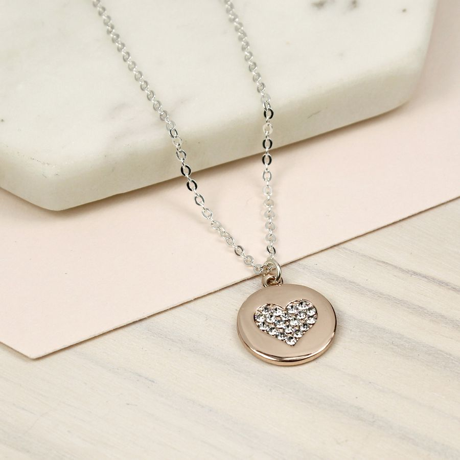 Round disc necklace in a pretty rose gold style finish with a heart inlay dorned with clear faceted crystals