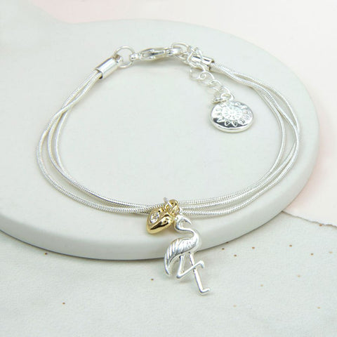 Silver plated triple chain bracelet with a gold silver crystal heart and a silver plated flamingo charm.