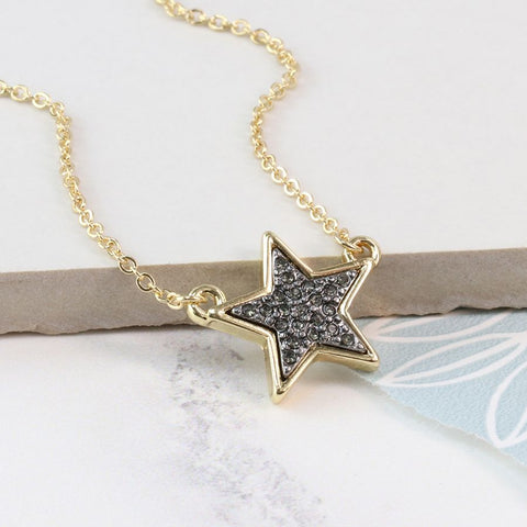 Gold-plated split chain necklace with a golden star pendant featuring a black enamel sparkle centre.