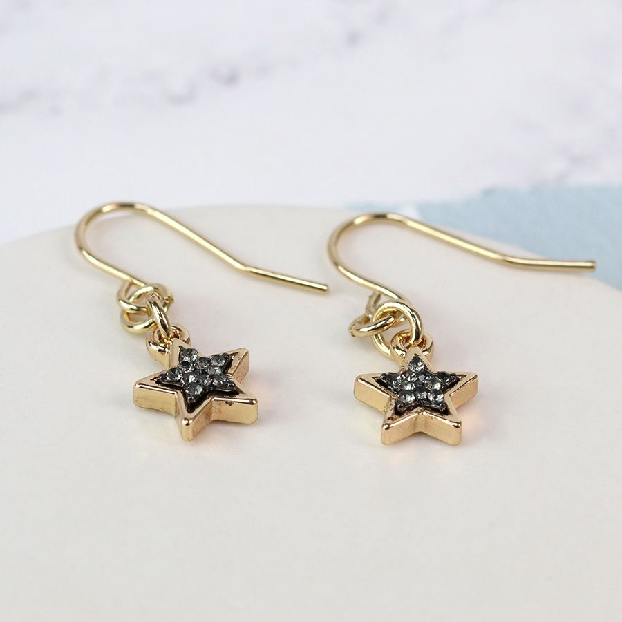 Dainty gold-plated star drop earrings featuring a black enamel sparkle centre, with gold plated earring hook wires.